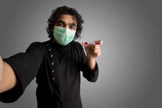 Junger mann, der ein selfie mit einem reagenzglas mit blutprobe für coronavirus- oder 2019-ncov-analyse nimmt.