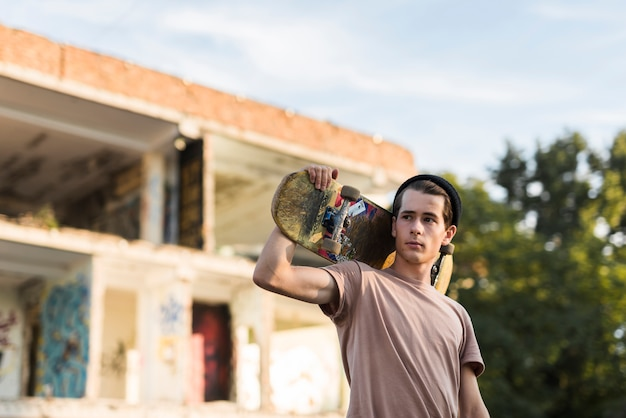 Junger mann, der ein skateboard anhält