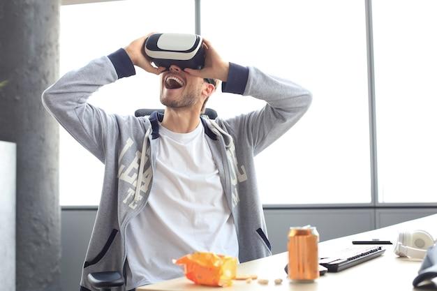 Junger mann, der ein spiel mit einem virtual-reality-headset im spielclub spielt.
