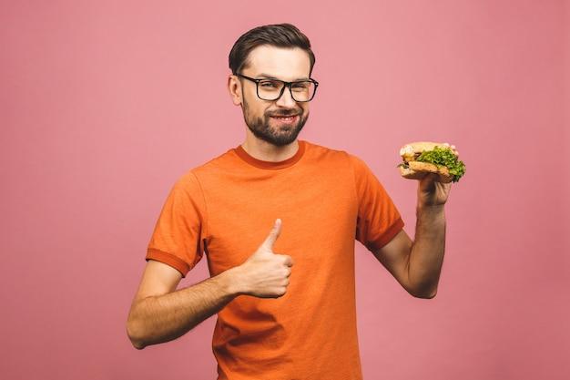 Junger mann, der ein stück hamburger hält. student isst fast food. sehr hungriger typ. daumen hoch.