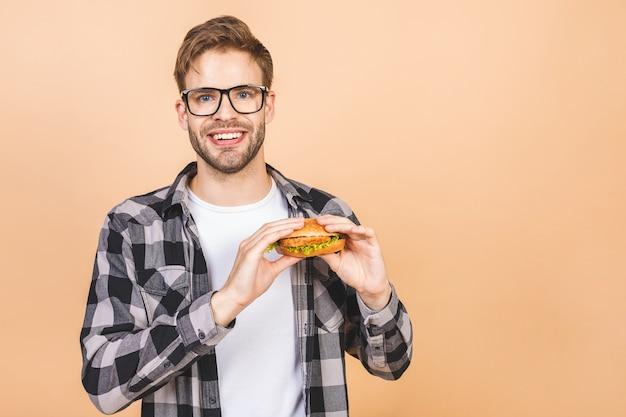 Junger mann, der ein stück hamburger hält