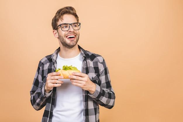 Junger mann, der ein stück sandwich hält