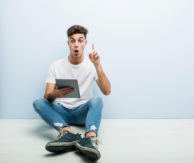 Junger mann, der ein tablettensitzen innen hält, etwas großartige idee, konzept der kreativität habend.