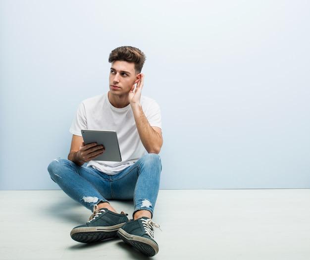 Junger mann, der ein tablettensitzen innenversuchen zum hören eines klatsches hält.