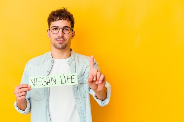 Junger mann, der ein veganes lebensplakat lokalisiert hält, das nummer eins mit finger zeigt