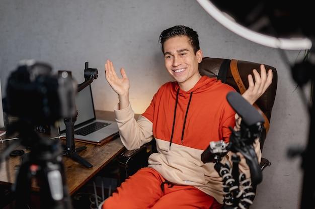 Junger mann, der ein video aufzeichnet, das mit der kamera mit allen ausrüstungen herum spricht. youtuber, lehre, vlog-konzept.