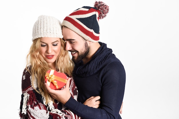 Junger mann, der ein weihnachtsgeschenk an seine frau unter schnee kleider mit winterkleidung auf weißem hintergrund geben