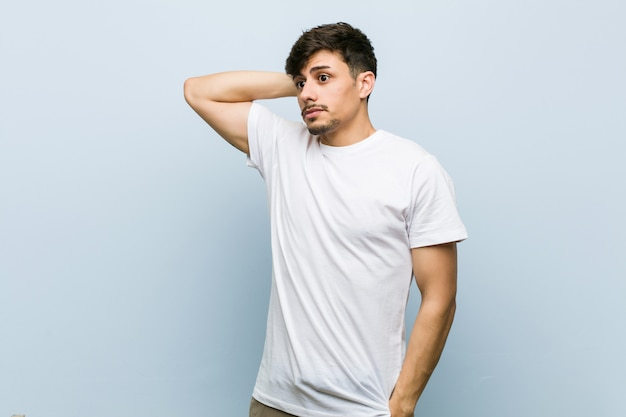 Junger mann, der ein weißes t-shirt berührt zurück vom kopf trägt, eine wahl denkt und trifft
