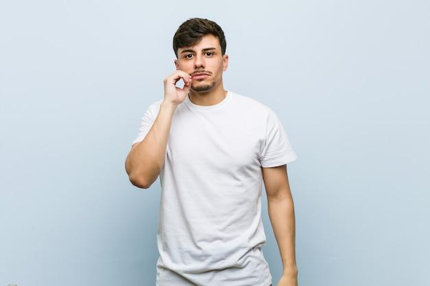 Junger mann, der ein weißes t-shirt mit den fingern auf den lippen trägt, die ein geheimnis halten
