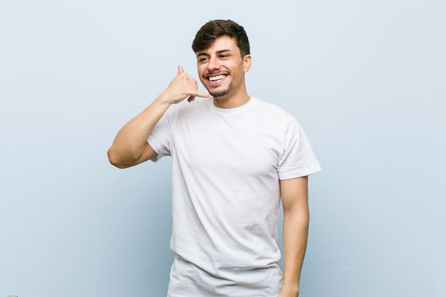 Junger mann, der ein weißes t-shirt trägt, das eine handy-anrufgeste mit fingern zeigt