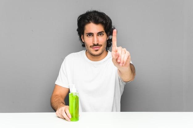 Junger mann, der eine aloe-vera-flasche hält, die nummer eins mit finger zeigt.