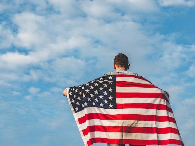 Junger mann, der eine amerikanische flagge wellenartig bewegt