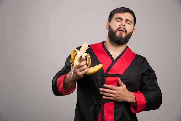 Junger mann, der eine banane auf grauer wand isst.