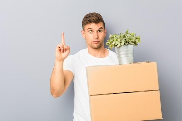 Junger mann, der eine bewegung hält, die kisten hält, die nummer eins mit finger zeigen.