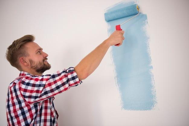Junger mann, der eine blaue wand malt