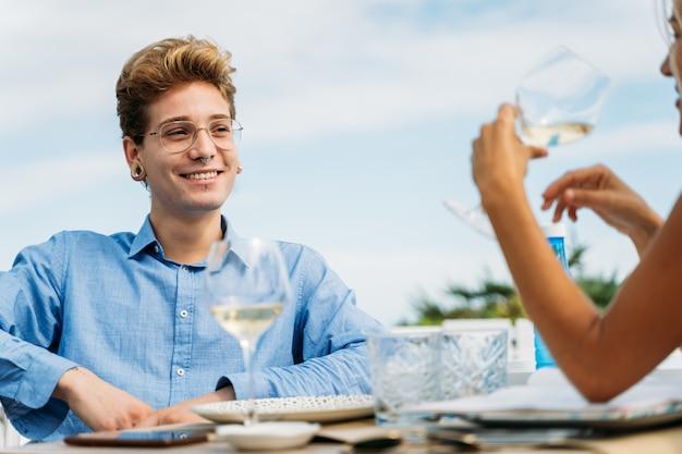 Junger mann, der eine blonde frau betrachtet, die ein glas wein hält, das an einem tisch sitzt