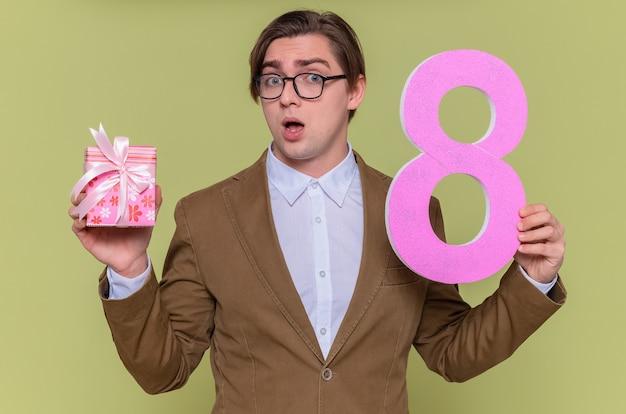 Junger mann, der eine brille hält, die nummer acht aus pappe und gegenwart hält, betrachtet den glücklichen und überraschten internationalen frauentag, der über grüner wand steht