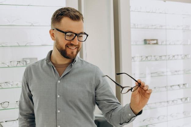 Junger mann, der eine brille im optikgeschäft wählt