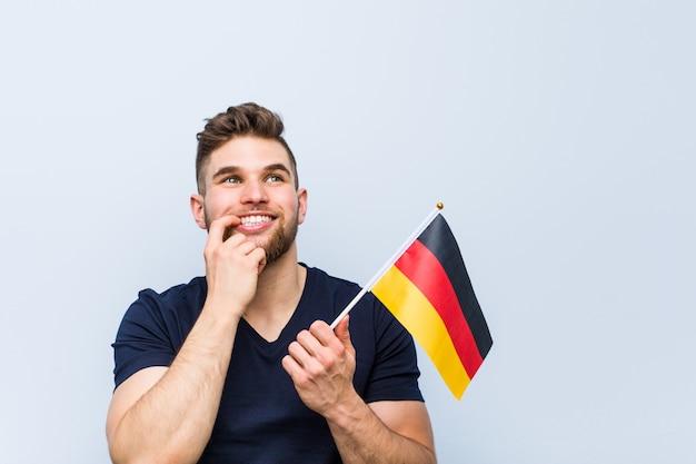 Junger mann, der eine deutsche flagge hält, entspannte sich und dachte an etwas, das einen kopienraum betrachtete