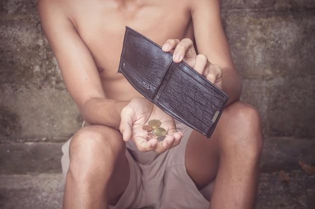 Junger mann, der eine emply geldbörse hält