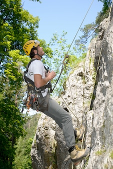 Junger mann, der eine felsenwand klettert