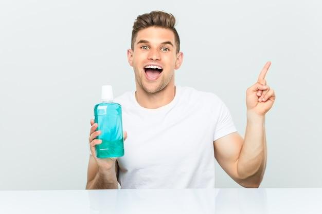Junger mann, der eine flasche mundwasser hält