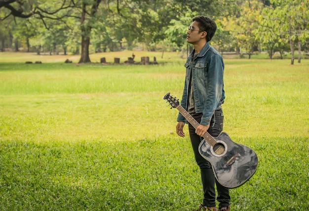 Junger mann, der eine gitarre anhält
