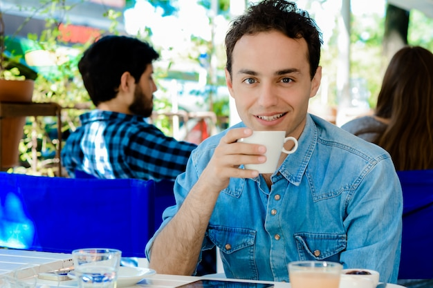 Junger mann, der eine kaffeepause macht