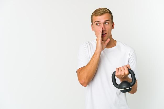 Junger mann, der eine kettlebell hält, die ein geheimnis erzählt