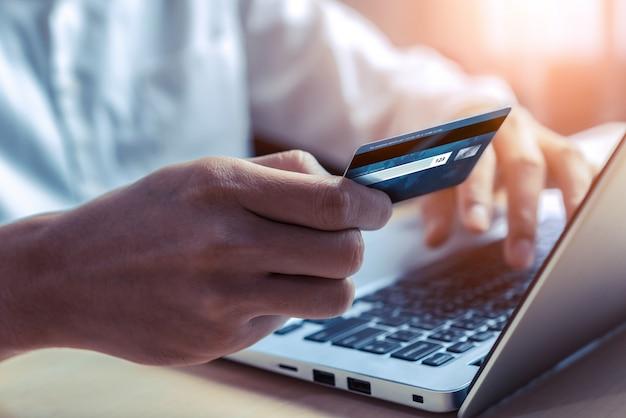 Junger mann, der eine kreditkarte für das on-line-einkaufen verwendet