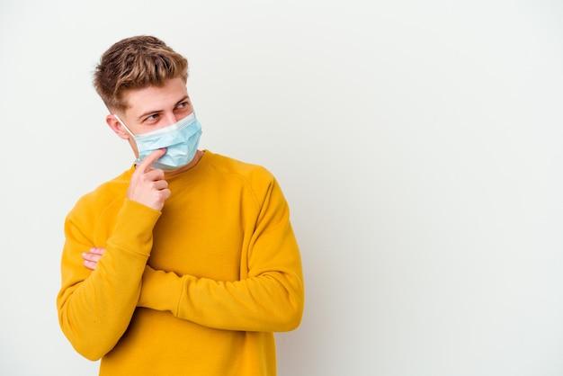 Junger mann, der eine maske für coronavirus isoliert trägt