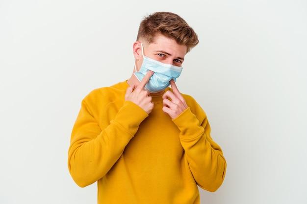 Junger mann, der eine maske für coronavirus trägt, isoliert auf weißem hintergrund, der zwischen zwei optionen zweifelt.