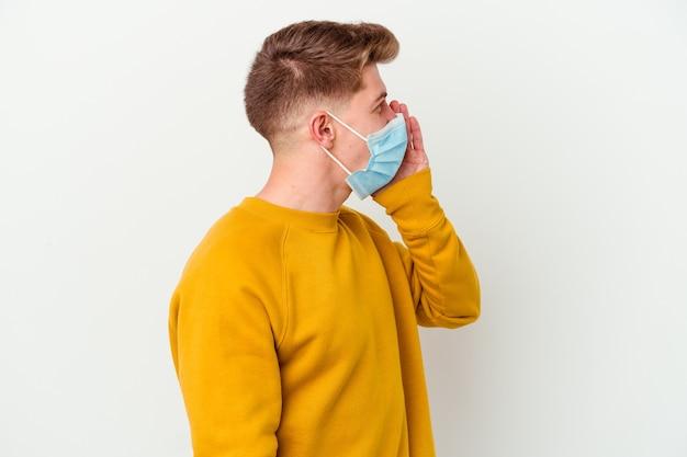 Junger mann, der eine maske für coronavirus trägt, isoliert auf weißer wand, die handfläche nahe geöffnetem mund schreit und hält.