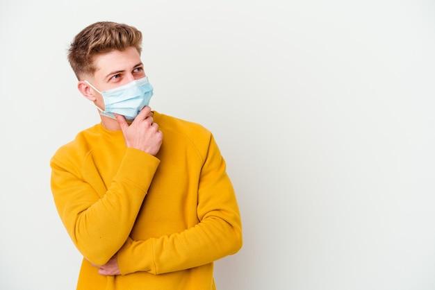 Junger mann, der eine maske für coronavirus trägt, isoliert auf weißer wand, die seitwärts mit zweifelhaftem und skeptischem ausdruck schaut.