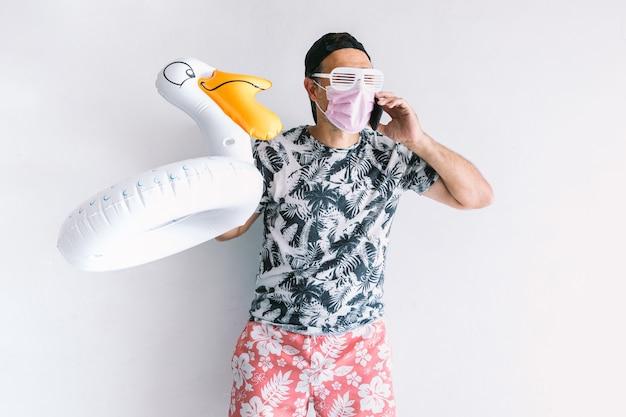 Junger mann, der eine maske trägt, um sich im urlaub vor covid-19 zu schützen, ein florales hemd und eine mütze trägt, einen entleinschwimmer hält und bei tageslicht an einer weißen wand mit dem handy spricht