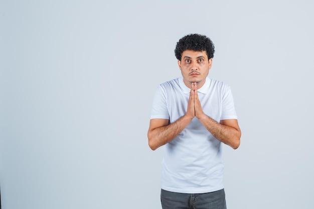 Junger mann, der eine namaste-geste in weißem t-shirt und jeans zeigt und ernst aussieht, vorderansicht.