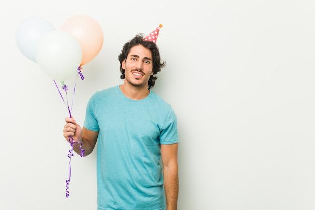 Junger mann, der eine partei hält, die ballons hält, die zuversichtlich mit verschränkten armen lächeln