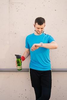 Junger mann, der eine pause macht - fitnesskonzept in der stadt.