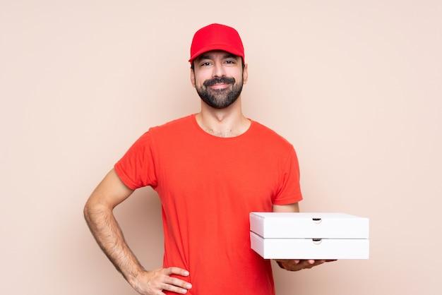 Junger mann, der eine pizza aufwirft mit den armen an der hüfte und am lächeln hält