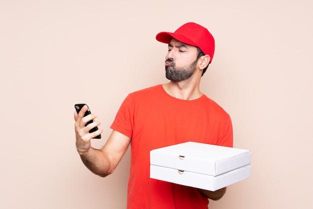 Junger mann, der eine pizza denkt und eine mitteilung sendet hält