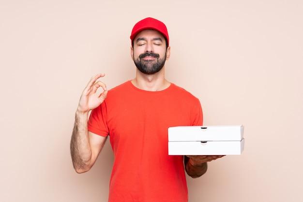 Junger mann, der eine pizza in der zenhaltung hält