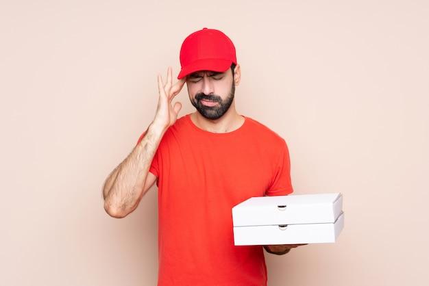 Junger mann, der eine pizza mit kopfschmerzen hält