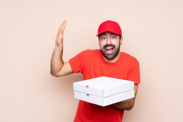 Junger mann, der eine pizza nervös und erschrocken hält