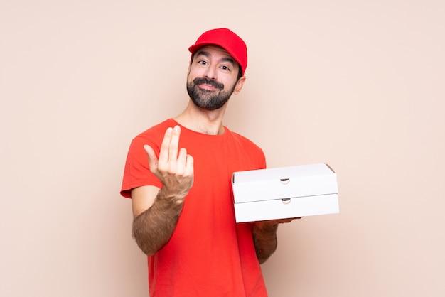 Junger mann, der eine pizza über dem lokalisierten hintergrund einlädt, mit der hand zu kommen hält. schön, dass sie gekommen sind