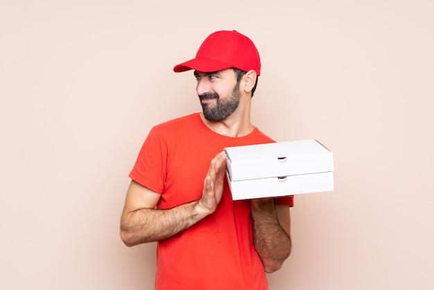 Junger mann, der eine pizza über dem lokalisierten hintergrund entwirft etwas hält