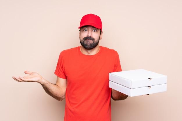 Junger mann, der eine pizza über dem lokalisierten hintergrund hat zweifel beim anheben von händen hält