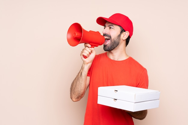 Junger mann, der eine pizza über dem lokalisierten hintergrund schreit durch ein megaphon hält