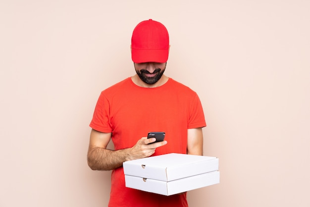 Junger mann, der eine pizza über dem lokalisierten senden einer mitteilung mit dem mobile hält