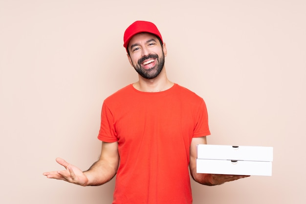Junger mann, der eine pizza über dem lokalisierten wandlächeln hält