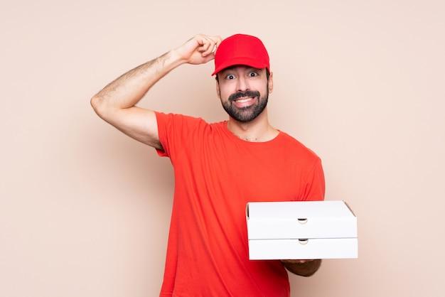 Junger mann, der eine pizza über der lokalisierten wand hat zweifel beim verkratzen des kopfes hält
